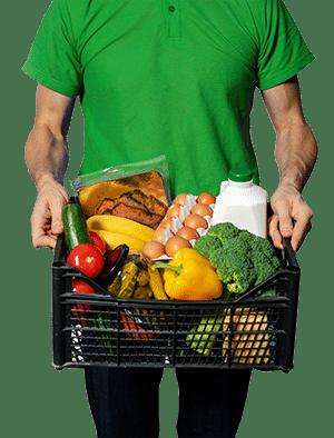 Homme tient dans ses mains un panier de courses avec fruits, légumes, œufs, etc.
