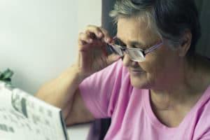 Une dame agée tient ses lunette en lisant le journal