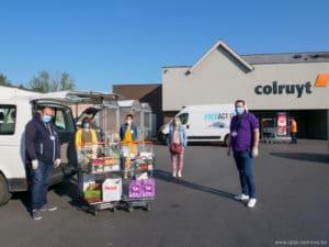 Cinq personnes devant le magasin Colruyt avec deux caddys remplis de courses