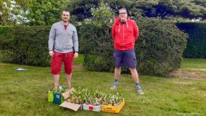 Deux membres du Club Human Impact dans un jardin avec leur récolte de muguet