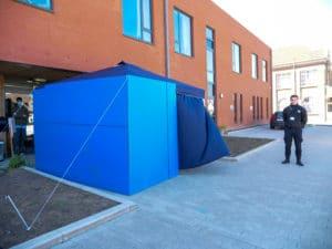 Une tonnelle bleue est placée devant la Home Sacré Cœur, un agent de sécurité monte la garde