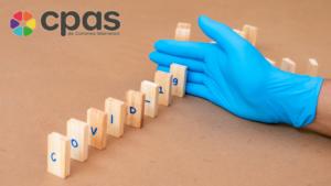 Une main gantée bloque un domino qui chute sur lequel est écrit Covid-19